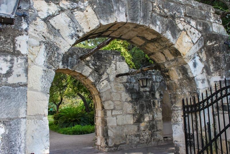 Vecchi pareti di pietra e archi con gli alberi e lanterne di attaccatura e delle viti e un portone sbagliato del ferro fotografia stock