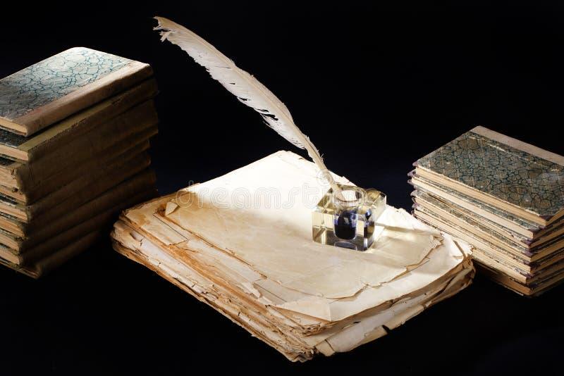 Vecchi penna stilografica, libri e calamaio d'annata su un fondo nero immagini stock