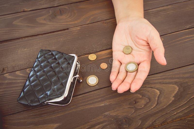Vecchi portafoglio e monete vuoti nelle mani Borsa vuota d'annata e monete in mani delle donne Concetto di povertà Fallimento immagini stock libere da diritti