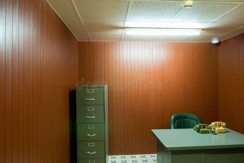 Vecchi scrittorio e sedia in piccolo ufficio con i telefoni rotatori d'annata, S fotografia stock