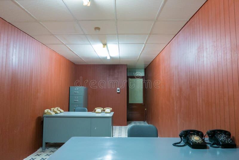 Vecchi scrittorio e sedia in piccolo ufficio con i telefoni rotatori d'annata, S fotografie stock
