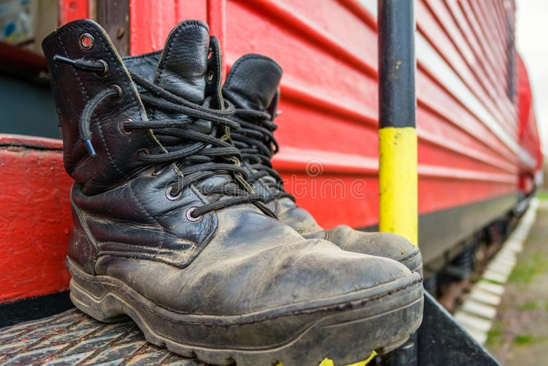 Vecchi stivali del pompiere sui precedenti del treno del fuoco rosso immagine stock libera da diritti