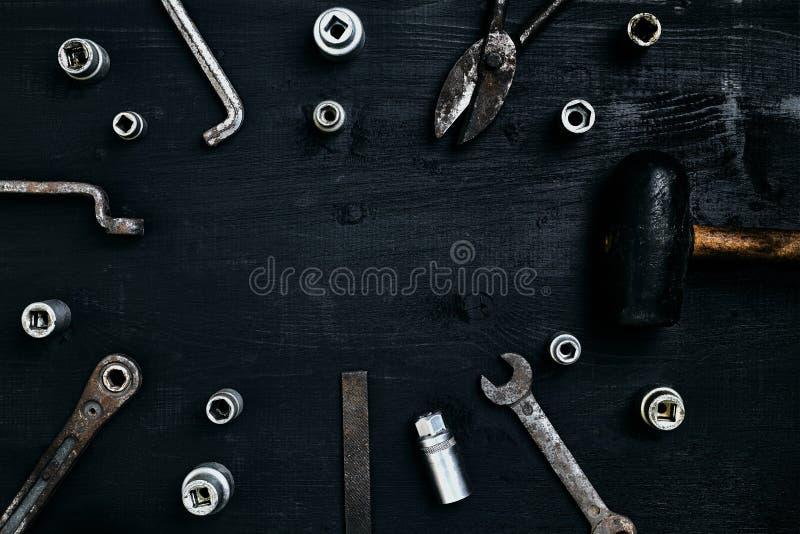 Vecchi, strumenti arrugginiti che si trovano su una tavola di legno Martello, scalpello, forbici del metallo, chiave, scalpello fotografia stock