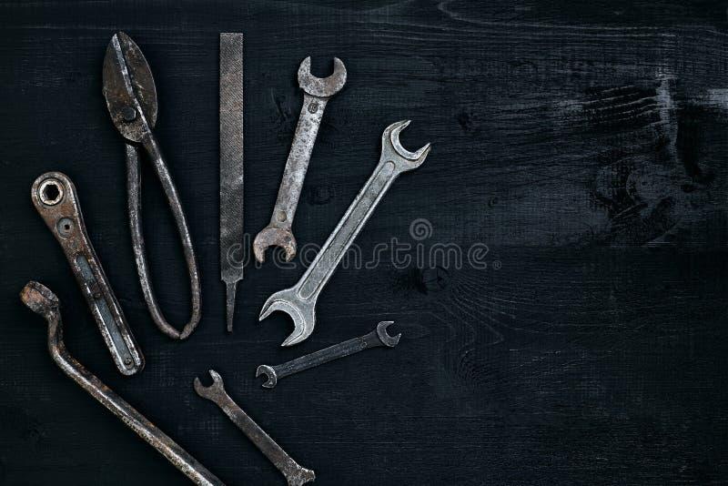 Vecchi, strumenti arrugginiti che si trovano su una tavola di legno nera Martello, scalpello, forbici del metallo, chiave fotografia stock