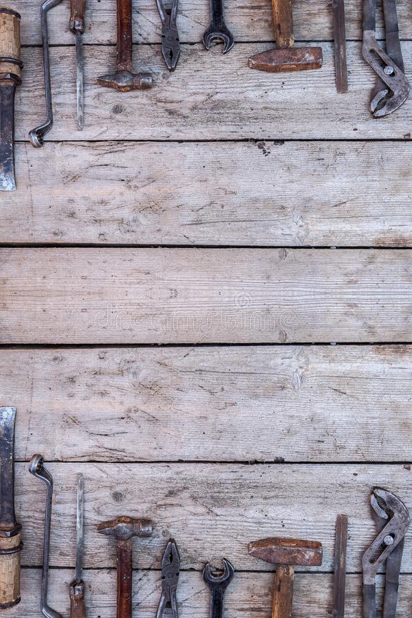 Vecchi, strumenti arrugginiti che si trovano su una tavola di legno nera Martello, scalpello, seghetto a mano per metalli, chiave immagini stock libere da diritti