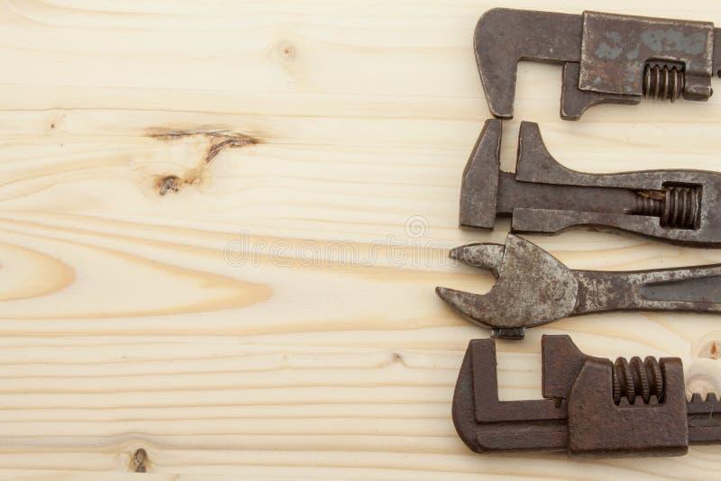 Vecchi strumenti arrugginiti dei meccanici su un fondo di legno Annunciando per i nuovi strumenti Strumenti di vendite fotografia stock libera da diritti