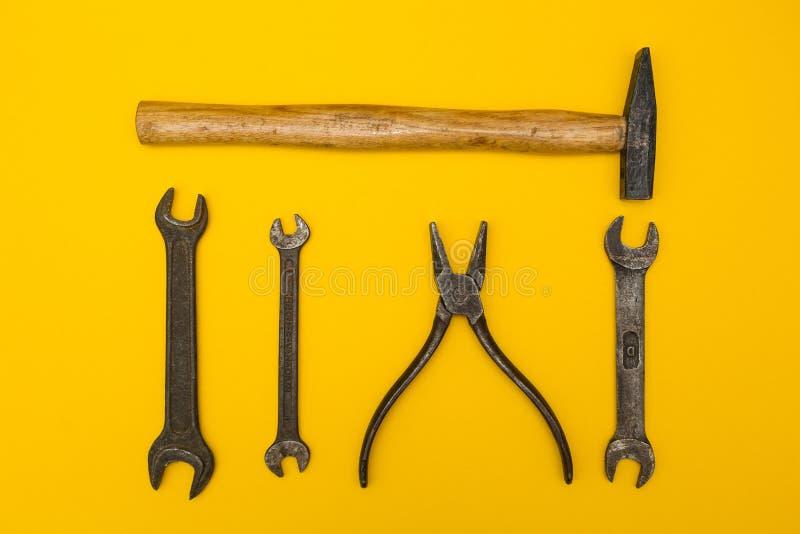 Vecchi strumenti arrugginiti su un fondo giallo fotografia stock