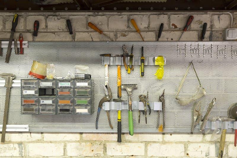 Vecchi strumenti che appendono sulla parete nell'officina del lavoro in metallo, aga dello scaffale dello strumento immagini stock