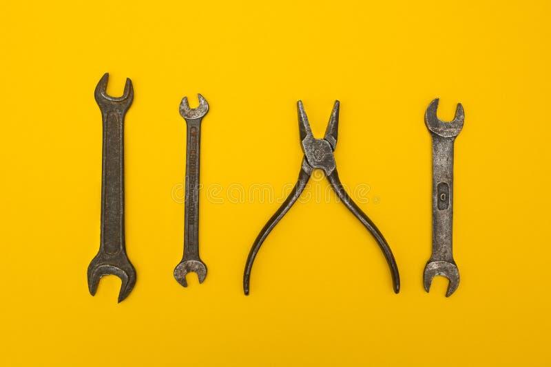 Vecchi strumenti isolati su fondo giallo immagine stock