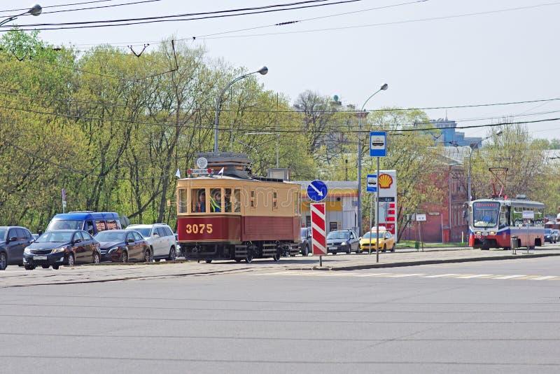 Vecchi tram ristabiliti e nuovi nel traffico cittadino moderno a Mosca fotografie stock