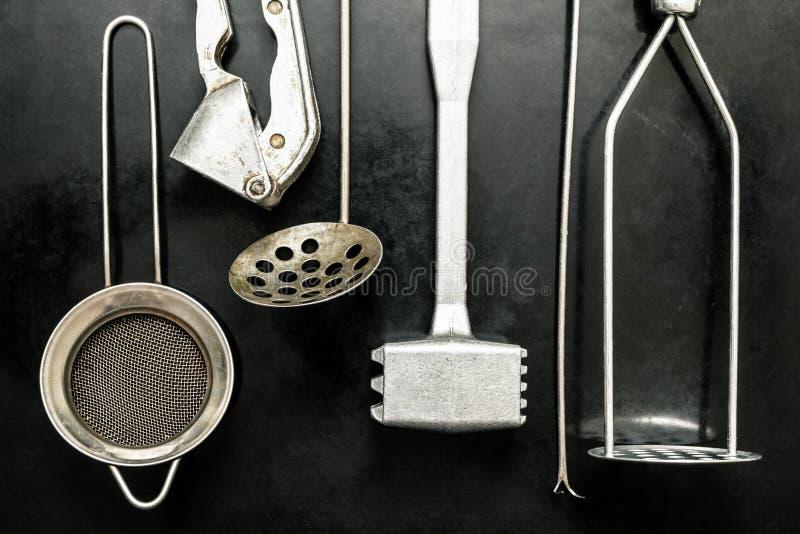 Vecchi utensili della cucina su un fondo nero immagini stock