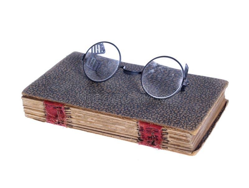 Vecchi vetri circolari sul libro antico fotografia stock libera da diritti