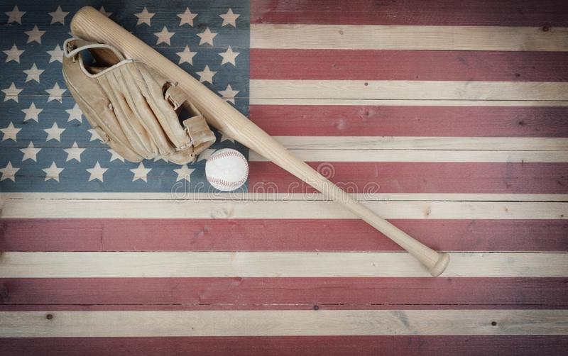 Vecchia attrezzatura di baseball americana sulla regolazione di legno d'annata della bandiera degli Stati Uniti fotografia stock