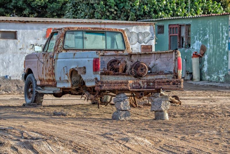 Vecchia automobile abbandonata arrugginita nessun gomme fotografia stock