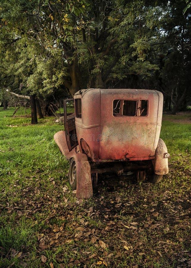 vecchia automobile abbandonata in un parco autunnale fotografia stock