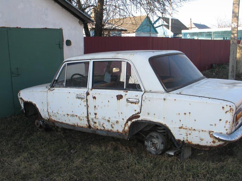 vecchia automobile bianca arrugginita senza ruote all'aperto fotografia stock