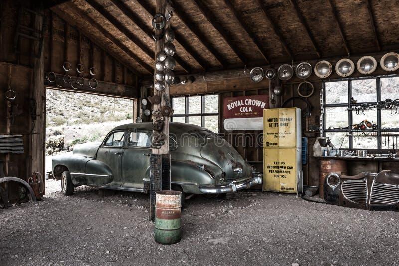 Vecchia automobile d'annata arrugginita nel garage abbandonato del meccanico fotografia stock libera da diritti