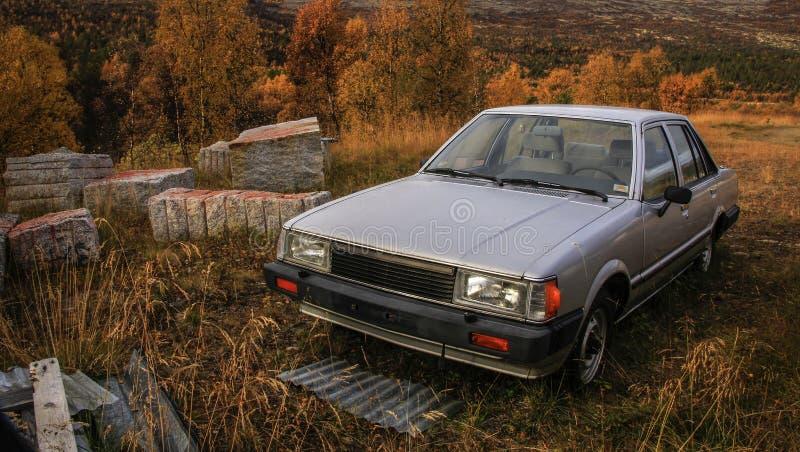 Vecchia automobile dimenticata nella foresta fotografia stock libera da diritti
