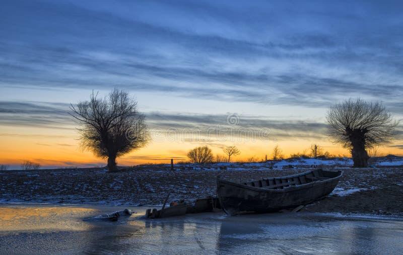 Vecchia barca al tramonto sul Danubio nell'inverno fotografia stock