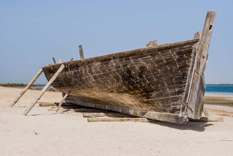 Vecchia barca da legno che sta sulla sabbia fotografie stock