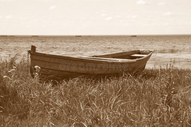 Vecchia barca di legno sulla banca del lago fotografia stock
