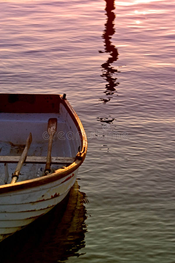 Vecchia barca di rematura con i remi sul mare durante il tramonto fotografie stock