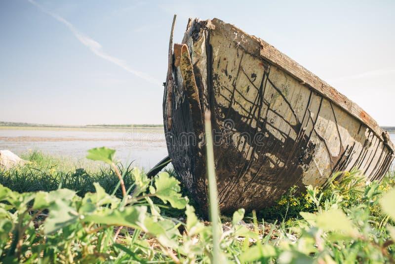 Vecchia barca rotta sulla riva del fiume in una giornata di sole immagine stock libera da diritti
