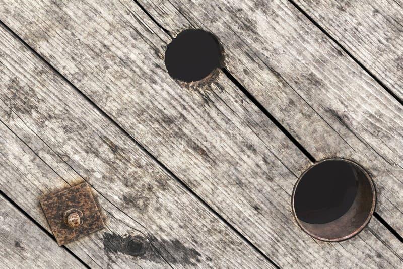 Vecchia barriera vuota incrinata stagionata di Pinewood di rinforzo con la rondella corrosa del dado esagonale e del quadrato del fotografia stock