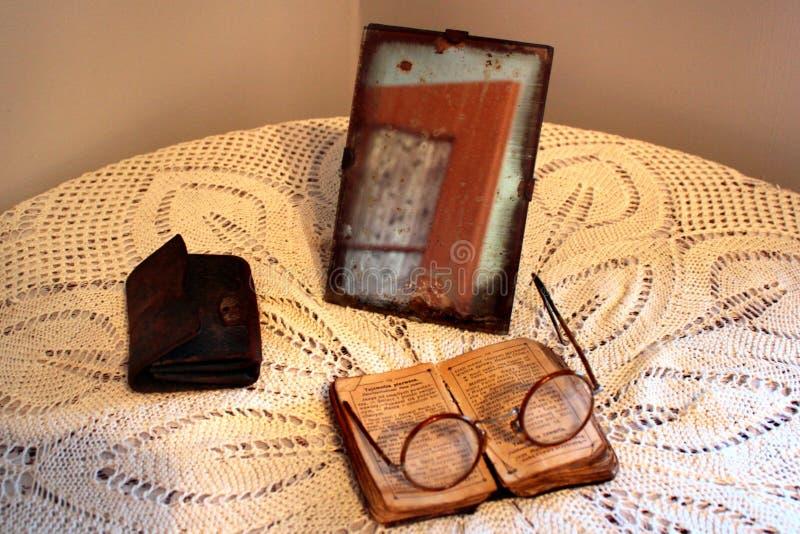 Vecchia bibbia polacca, retro occhiali e specchio d'annata su una tovaglia Concetto di vecchiaia, di senilità e di povertà immagini stock