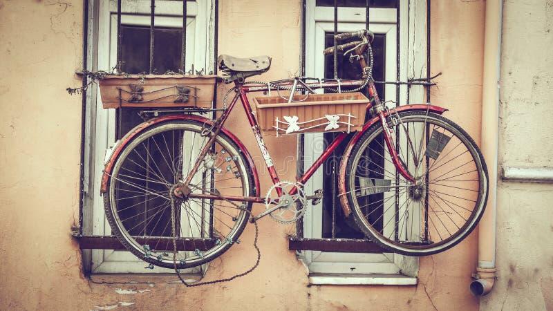 Vecchia bicicletta decorativa sulla finestra fotografia stock