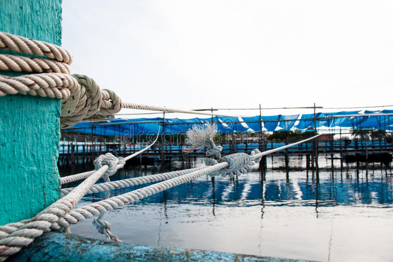 Vecchia bitta d'attracco arrugginita con le corde nautiche annodate fotografie stock