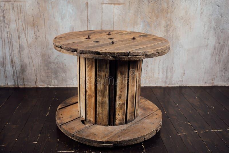 Vecchia bobina di legno contro il fondo del muro di cemento immagine stock libera da diritti