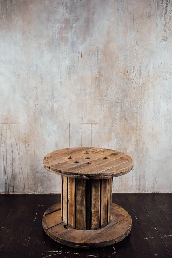 Vecchia bobina di legno contro il fondo del muro di cemento fotografia stock