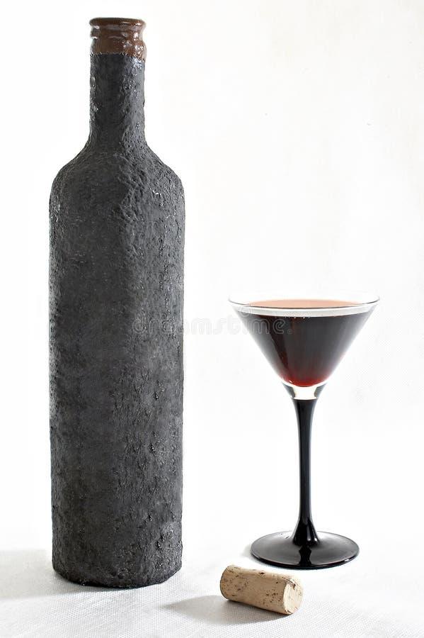Vecchia bottiglia di vino con una coppa piena di vino e di sughero immagine stock libera da diritti