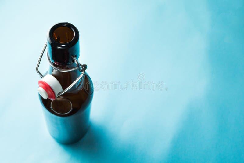 Vecchia bottiglia marrone con birra senza un'etichetta su un fondo blu Spazio per testo immagine stock