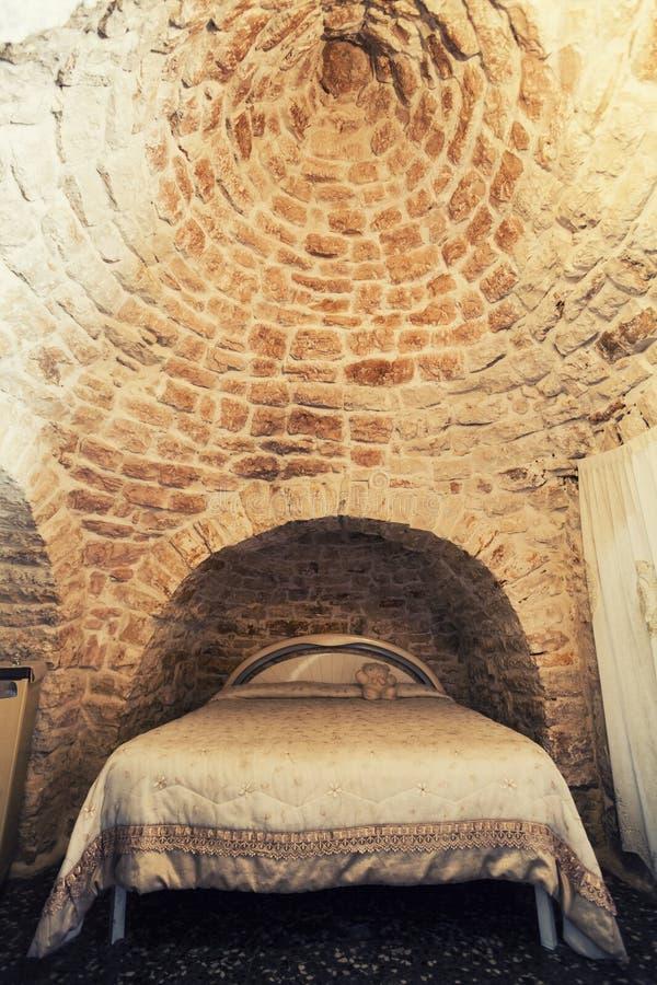 Vecchia camera da letto con letto matrimoniale in un Trullo in Italia, costruzione tipica del tetto immagine stock libera da diritti