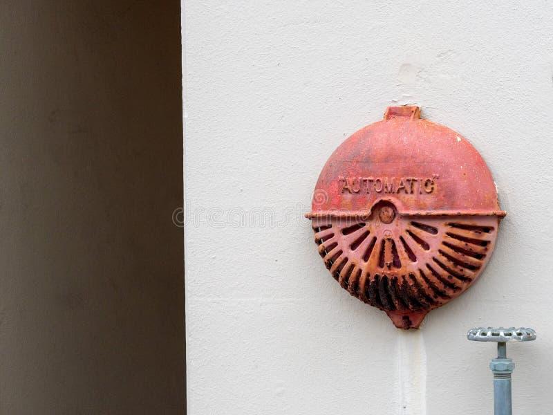 Vecchia campana di allarme antincendio arrugginita automatica che appende fuori del fabbricato industriale fotografie stock libere da diritti