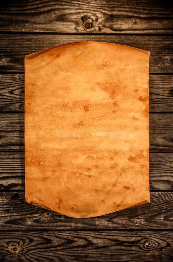 Vecchia carta in bianco contro lo sfondo di un legno invecchiato fotografia stock