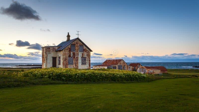 Vecchia casa abbandonata dell'azienda agricola alla mezzanotte in Islanda fotografia stock