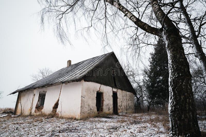 Vecchia casa abbandonata nell'orario invernale lithuania fotografia stock