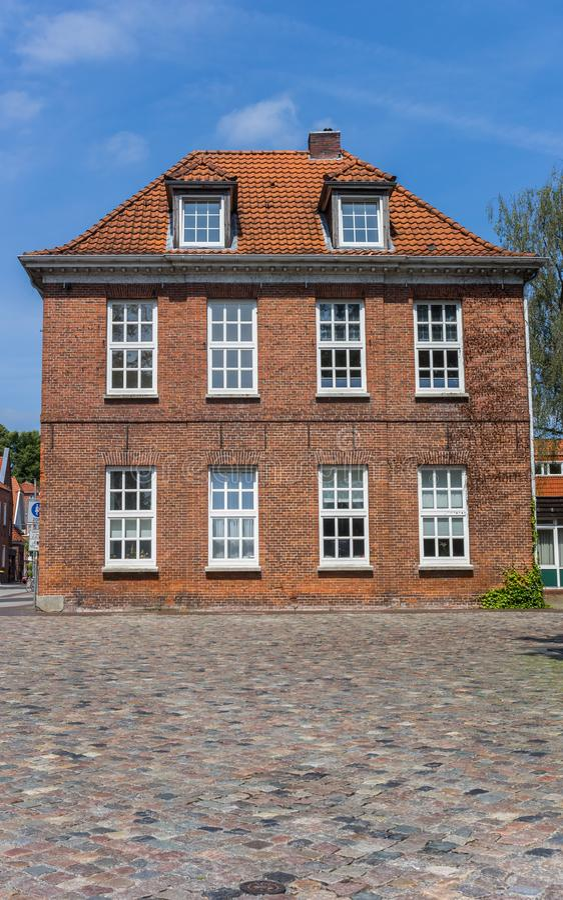 Vecchia casa ad una via cobblestoned in Aurich immagini stock