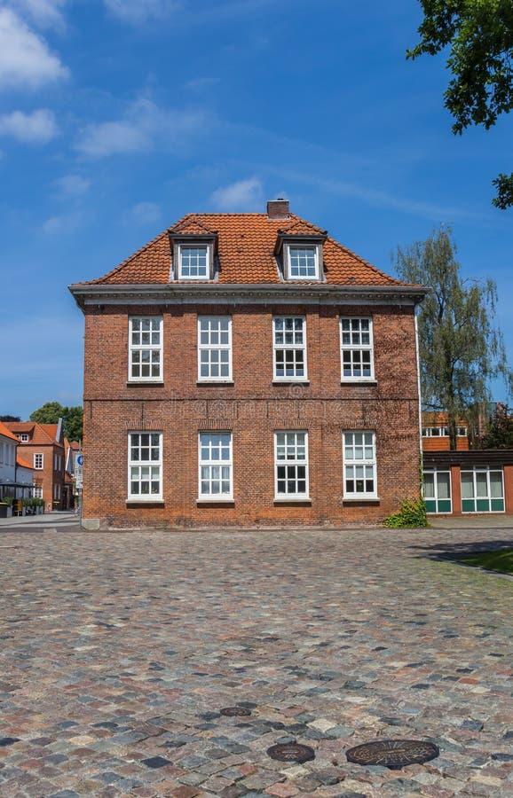 Vecchia casa ad una via cobblestoned in Aurich fotografie stock libere da diritti