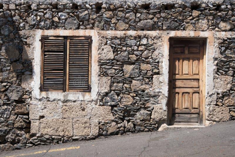 Vecchia casa con la porta di legno e la facciata di pietra naturale fotografia stock libera da diritti