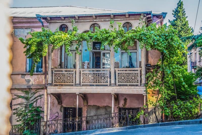 Vecchia casa di grunghe ornate a Tbilisi in Georgia ricoperta di vite di uva fotografia stock