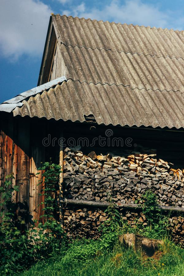 Vecchia casa di legno con il legno del fuoco sopra le montagne della collina in sole fotografie stock