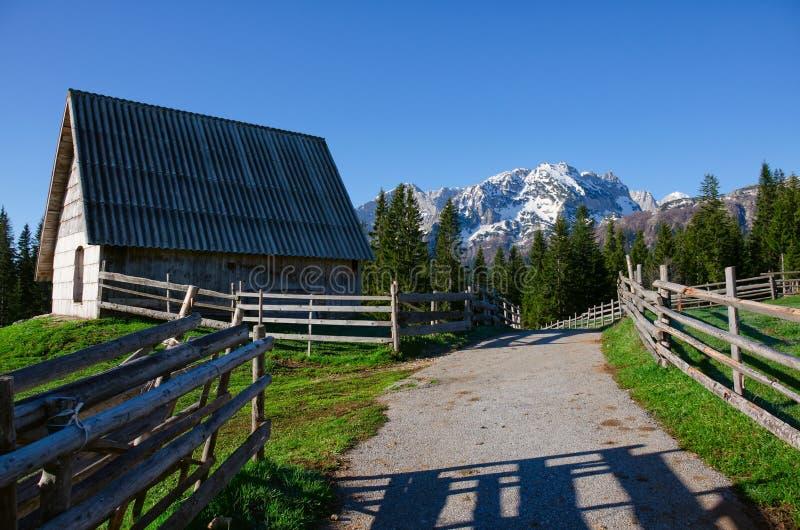 Vecchia casa di legno nel Montenegro Strada, recinto, montagne e foresta vicino fotografie stock libere da diritti