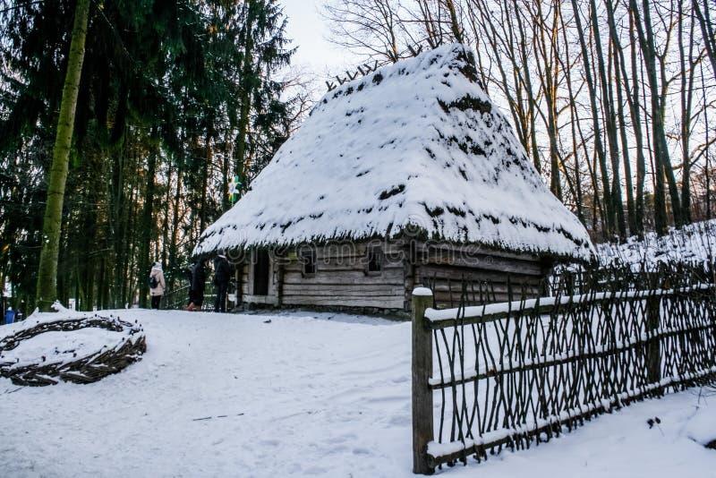 Vecchia casa di legno nevosa d'annata Inverno Montagne e foresta immagini stock libere da diritti