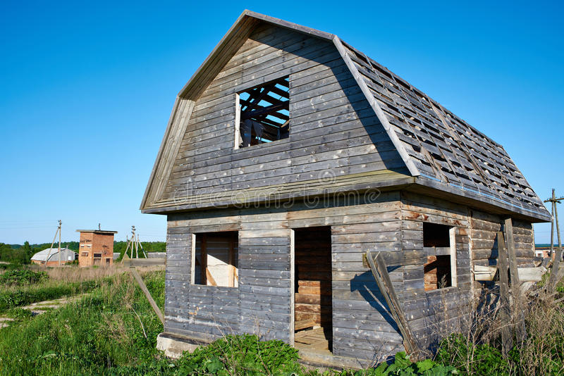 Vecchia casa di legno non finita in villaggio immagini stock