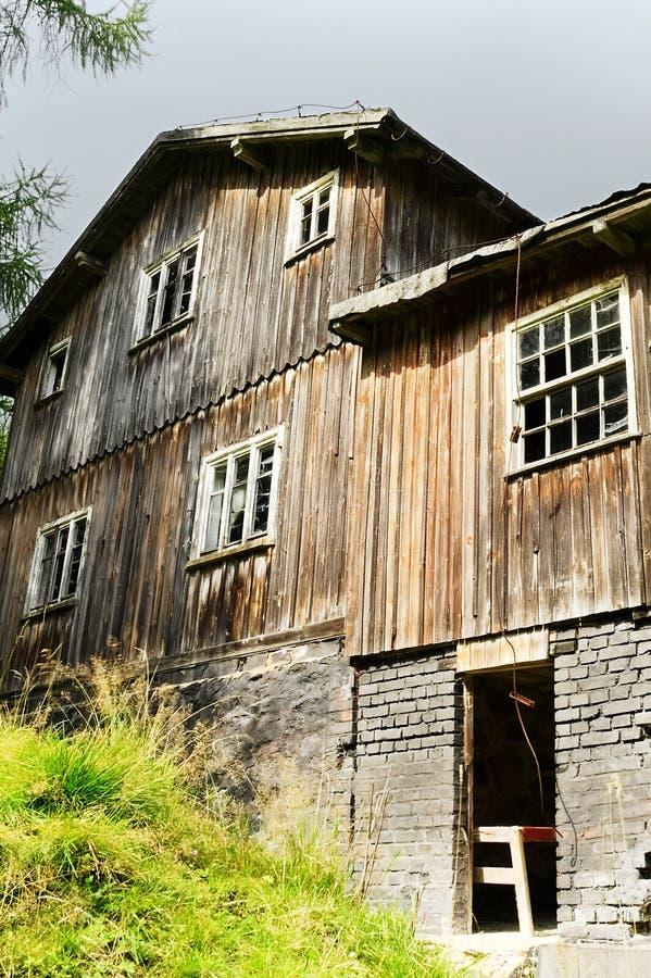 Vecchia casa di legno spaventosa abbandonata su una radura della foresta fotografia stock