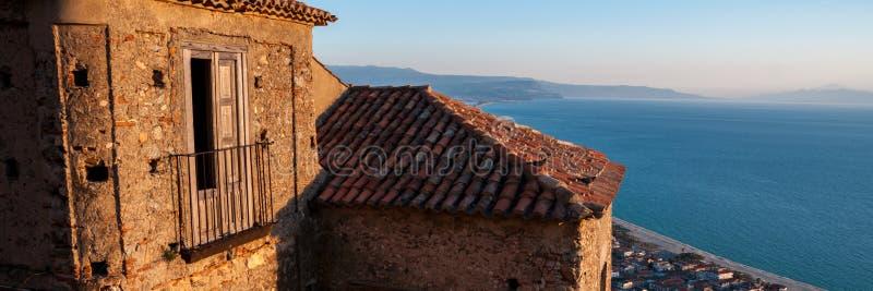 Vecchia casa di pietra italiana sopra la cittadina dal mare fotografia stock libera da diritti
